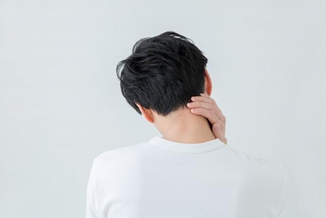 首の痛みを気にする男性の写真